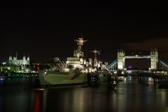 HMS Belfast, Tower Bridge and Tower of London. HMS Belfast, Tower Bridge and the Tower of London at night, London, UK Stock Images