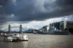 HMS Belfast und Turm-Brücke unter schwermütigen Himmeln Stockbild