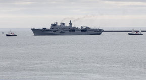 HMS Ocean returning to Plymouth. Harbour escorted by tug boats Stock Photos