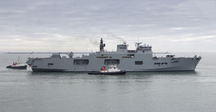 HMS Ocean returning to Plymouth. Harbour escorted by tug boats Stock Images