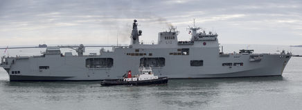 HMS Ocean returning to Plymouth with tug boat. The assault ship HMS Ocean returning to Plymouth harbour escorted by a tug boat Stock Photos