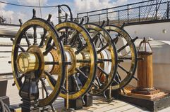 Upper steering wheels on HMS Warrior Portsmouth Docks. HMS Warrior is a 40-gun steam powered armoured Frigate. Built 1859 to 61. Armour plated iron hulled war Royalty Free Stock Images