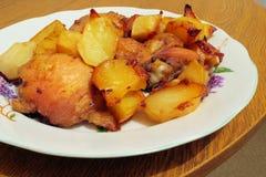 Höna som grillas med potatisar i plattan Arkivfoto
