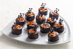Handmade chocolate bonbons. Topped with candied orange and piped chocolate for a luxury celebration stock photos