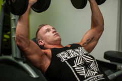 Hnadsome young man working out with dumbbells in fitness -  powe Stock Photos