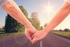 Händchenhalten des glücklichen Paars schließt oben Stockbilder