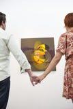 Händchenhalten des verheirateten Paars vor Malerei in der Kunstgalerie Stockfotografie