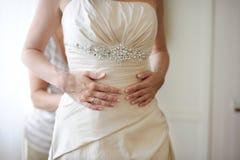 Hände der Braut beim Setzen des Hochzeitskleides Lizenzfreie Stockfotos