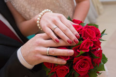 Hände des Bräutigams und der Braut auf rotem Hochzeitsblumenstrauß Lizenzfreie Stockbilder