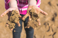 Hände des Kindes voll des nassen Sandes Stockbild