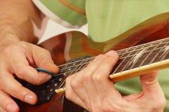 Hände des Mannes den Gitarrenabschluß oben spielend Lizenzfreies Stockfoto