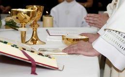 Hände des Priesters durch die Masse Stockfoto
