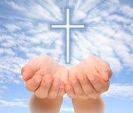Hände, die christliches Kreuz mit Lichtstrahlen anhalten Stockfotografie
