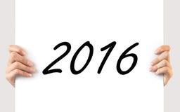 Hände, die ein weißes Brett 2016 halten Stockbild