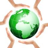 Hände, die einen Kreis mit grüner Erde bilden Lizenzfreie Stockfotos