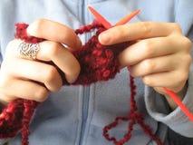 Hände, die einen magentaroten Schal stricken Stockbilder