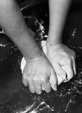 Hände, die einen Teig kneten Stockbild