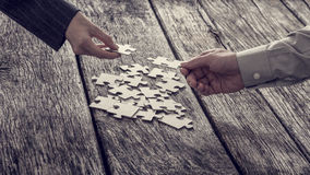 Hände, die für Puzzlespielstücke erreichen Stockbild