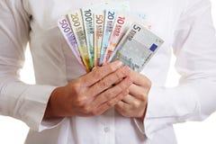 Hände, die Gebläse gebildet vom Euro anhalten Stockfotografie