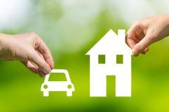 Hände, die herausgeschnittenes Papierauto und Haus als Symbol der Hypothek halten Stockbild