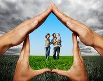 Hände, die junge Familie schützen Stockbild