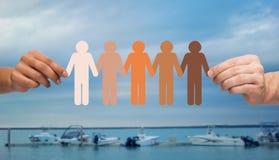 Hände, die Leutepiktogramm über Booten im Meer halten Stockfotos