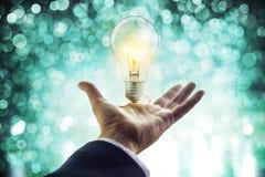 Hände eines Geschäftsmannes, der in Richtung zu zur Glühlampe, Geschäftskonzept erreicht Lizenzfreie Stockfotos