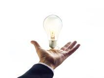 Hände eines Geschäftsmannes, der in Richtung zu zur Glühlampe, Geschäftskonzept erreicht Lizenzfreie Stockbilder