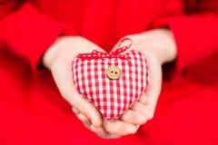 Hände eines Kindes, das ein rot-weißes Herz des Plaids Textilmit Knopf hält Stockfotografie