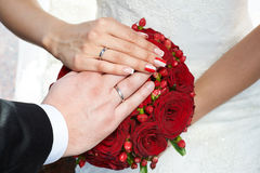 Hände mit Hochzeitsgoldringen und Blumenstrauß von roten Rosen Lizenzfreie Stockfotos