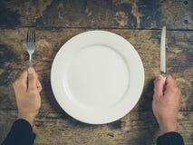 Hände mit Platte, Messer und Gabel Stockfotos