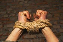 Hände oben gebunden mit Seil Stockfoto