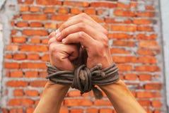 Hände oben gebunden mit Seil Stockfotos