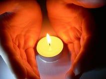 Hände und eine Kerze Stockfotografie