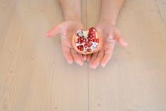 Hände und Granatapfel Stockfotos