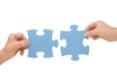 Hände und Puzzlespiel Stockfotos
