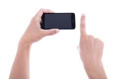 Hände unter Verwendung des intelligenten Mobiltelefons mit dem leeren Bildschirm lokalisiert auf whi Stockfoto