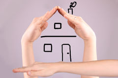 Hände, welche die Form von einem Haus auf Gray Background machen Stockfoto
