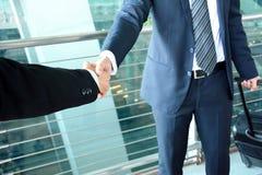 Händedruck von Geschäftsmännern am Flughafen - Dienstreisekonzept Lizenzfreies Stockfoto