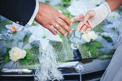 Händer av bruden och brudgummen bröllopbukett på Arkivfoto