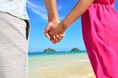 Händer för innehav för strandpar förälskade på bröllopsresa Arkivfoto