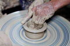 Händer på ett stycke av krukmakeri som göras av lera Fotografering för Bildbyråer