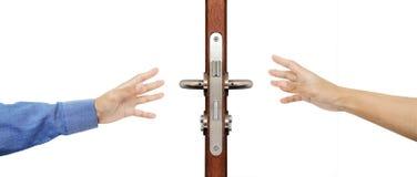 Händer som försöker att nå som griper dörrknoppen som isoleras på vit bakgrund Royaltyfri Fotografi