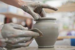 Händer som gör krukmakeri på ett hjul Arkivfoto