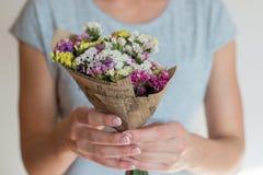 Händer som rymmer buketten av blommor Royaltyfri Bild