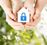 Händer som rymmer det pappers- huset med låset Royaltyfria Bilder