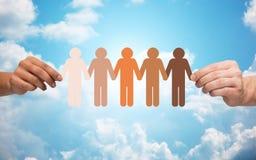 Händer som rymmer kedjan av folkpictogramen över himmel Arkivbilder