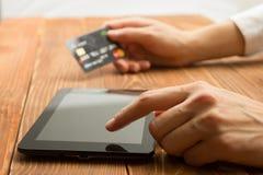 Händer som rymmer kreditkortmaskinskrivningnummer på minnestavlaPC:n som gör online-betalning hemmastadd trätabellen card grund s Arkivbilder