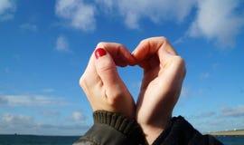 Händer som skapar en hjärta av förälskelse Arkivfoton