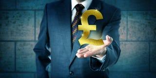 Händler Holding ein goldenes britisches Pfund Sterling Symbol Lizenzfreies Stockfoto